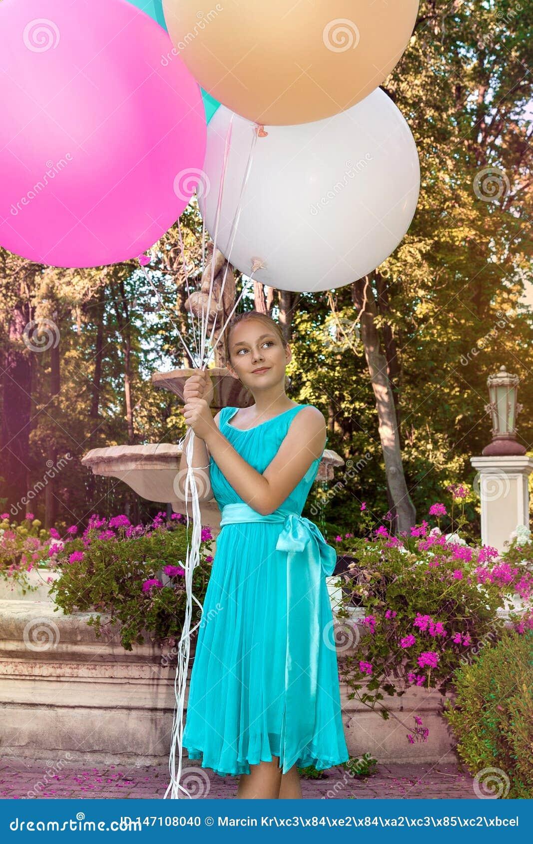 Милая маленькая девочка с большими красочными воздушными шарами идя в парк около городка - изображения