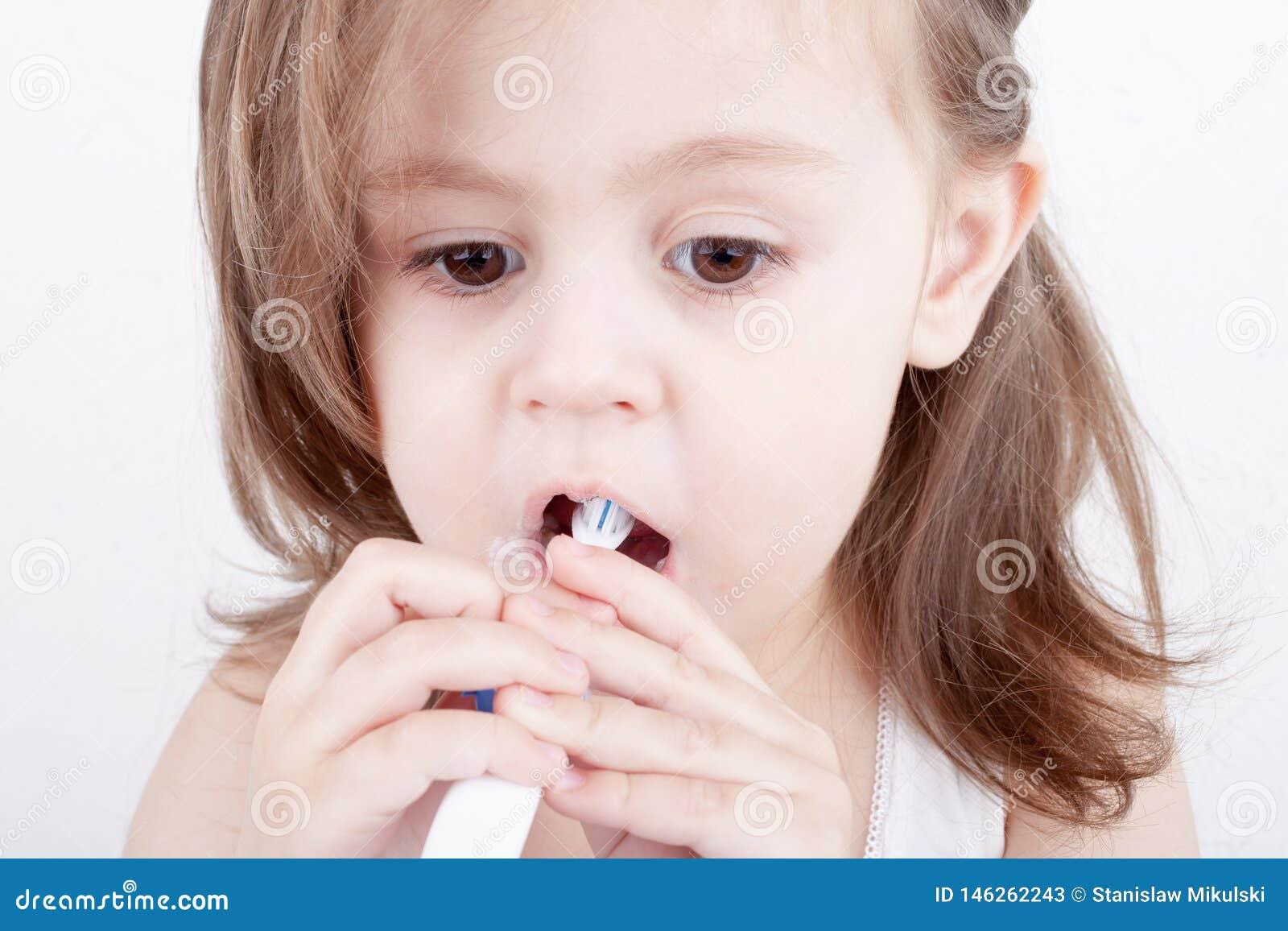 Милая маленькая девочка чистя ее зубы щеткой