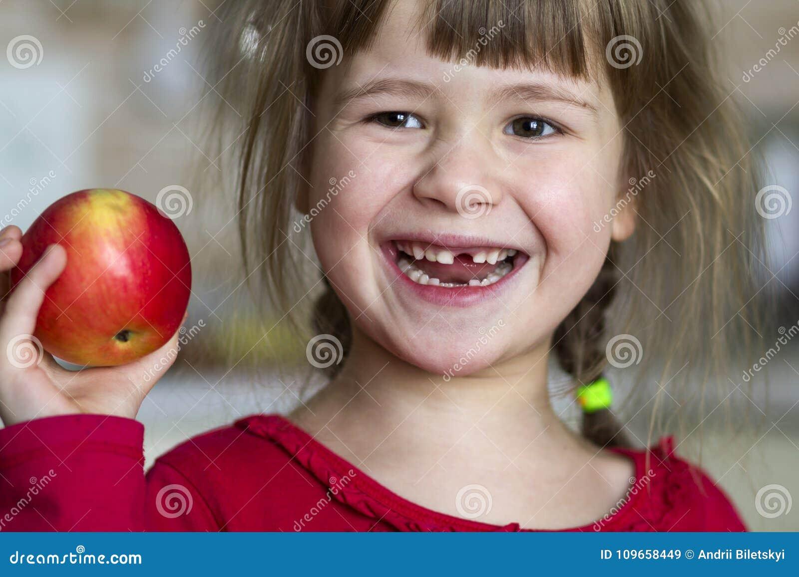 Милая маленькая курчавая беззубая девушка усмехается и держится красное яблоко Портрет счастливого младенца есть красное яблоко Р
