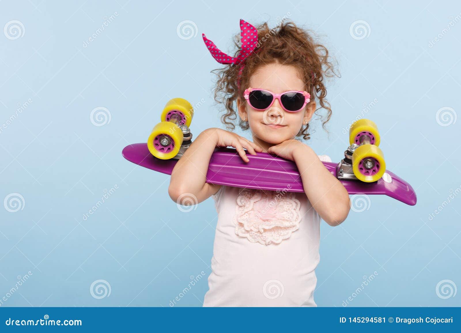 Милая маленькая курчавая девушка, в солнечных очках, держа в студии со