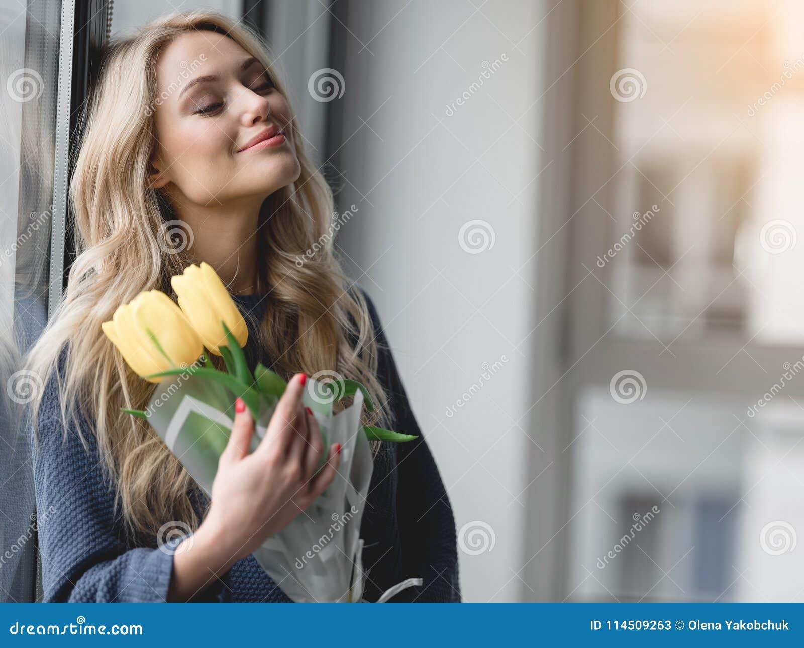 Милая молодая женщина держа желтые тюльпаны