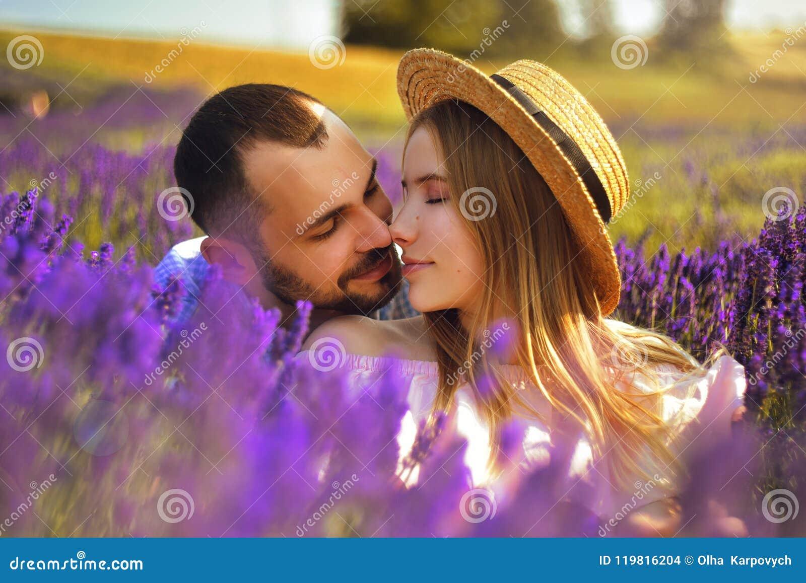 Милая молодая пара в влюбленности в поле лаванды цветет Насладитесь моментом счастья и влюбленности в поле лаванды Поцелуй