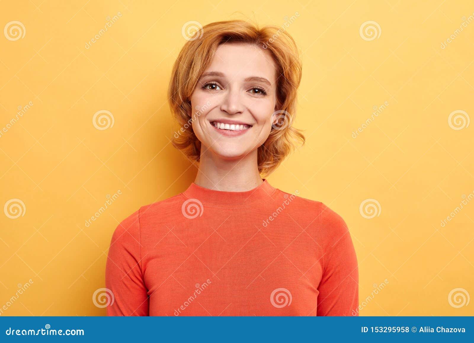 Милая положительная девушка усмехаясь смотрящ камеру над желтой предпосылкой