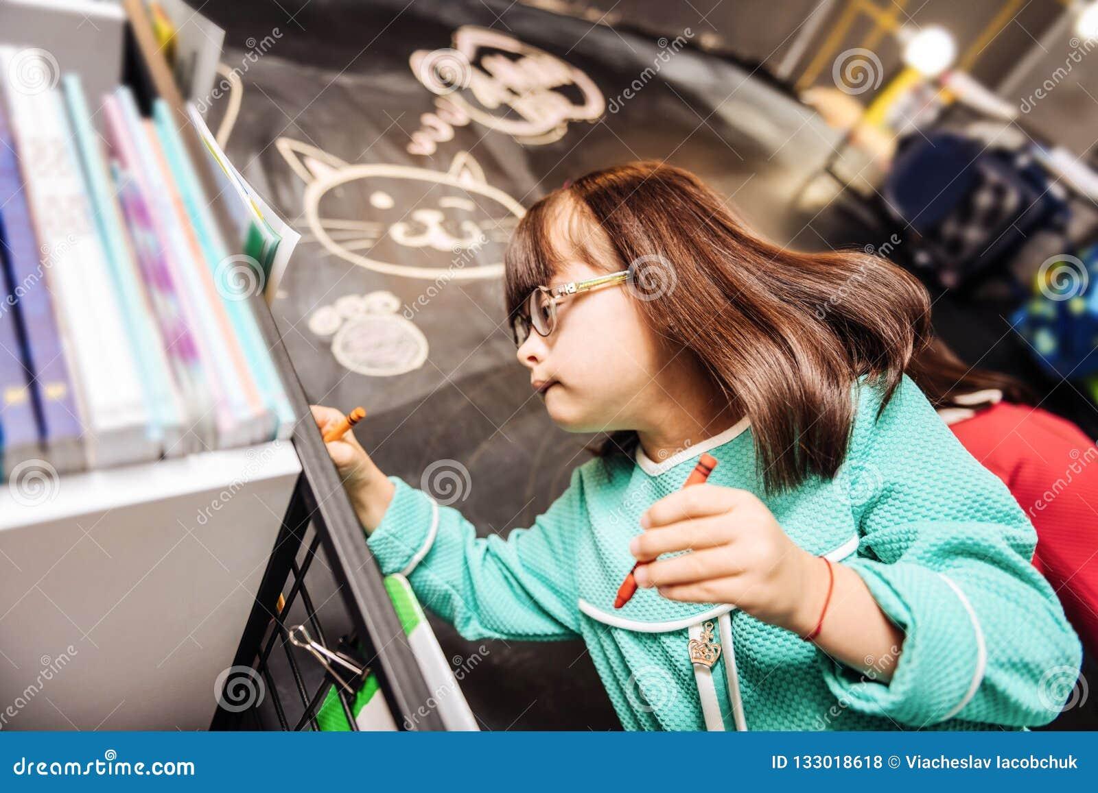 Милая приятная девушка с Синдромом Дауна рисуя милого кота на классн классном