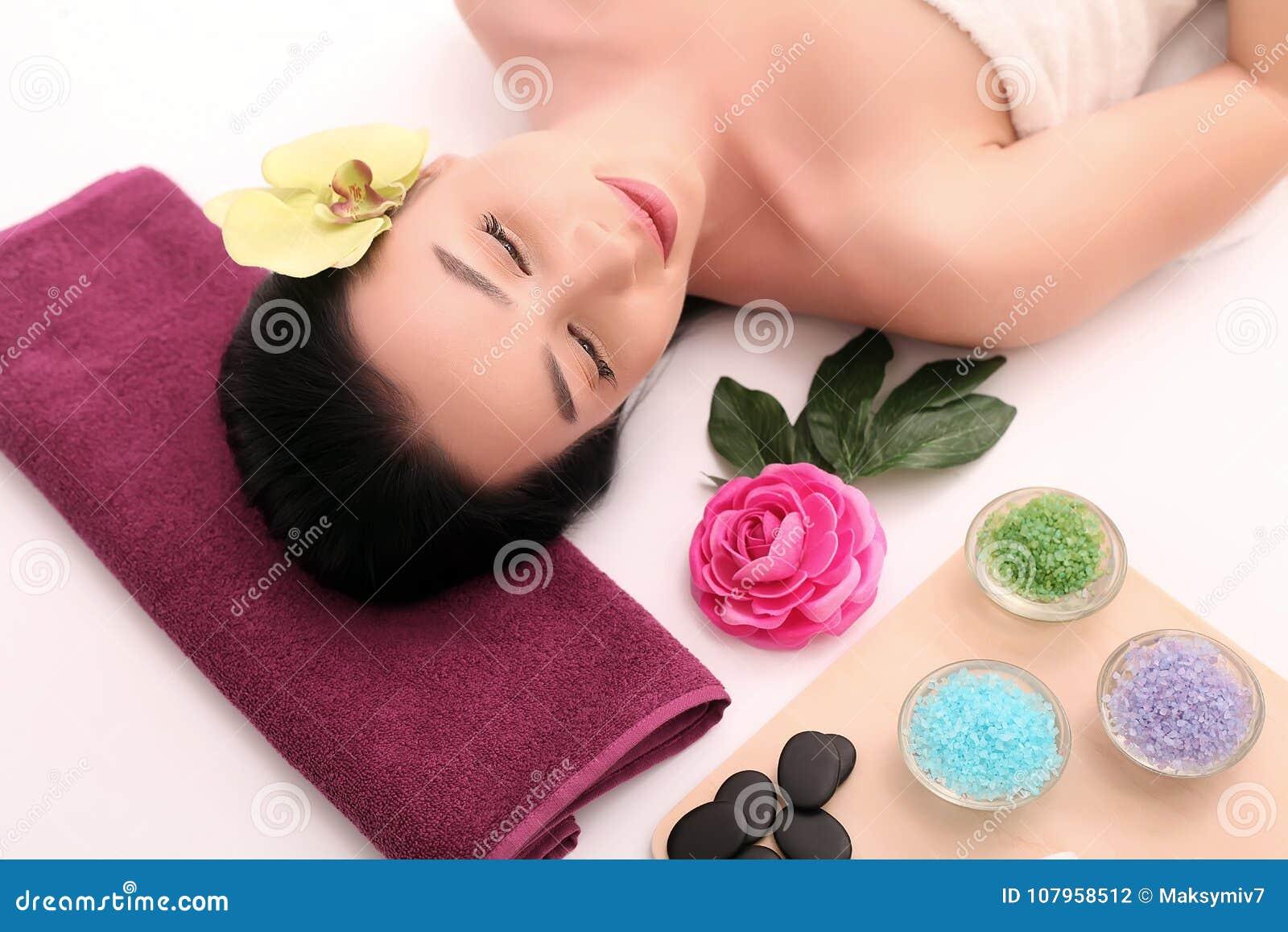 Милая расслабленная молодая женщина кладя в салон курорта с закрытыми глазами