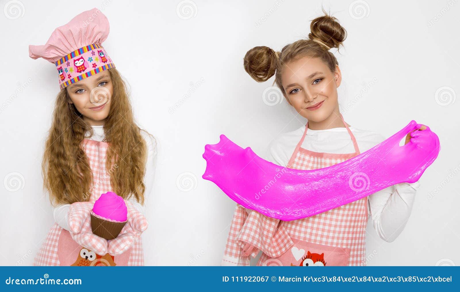 Милая смешная девушка с шламом в кухне Девушка варит и печет ее булочки, делает торт и шлам
