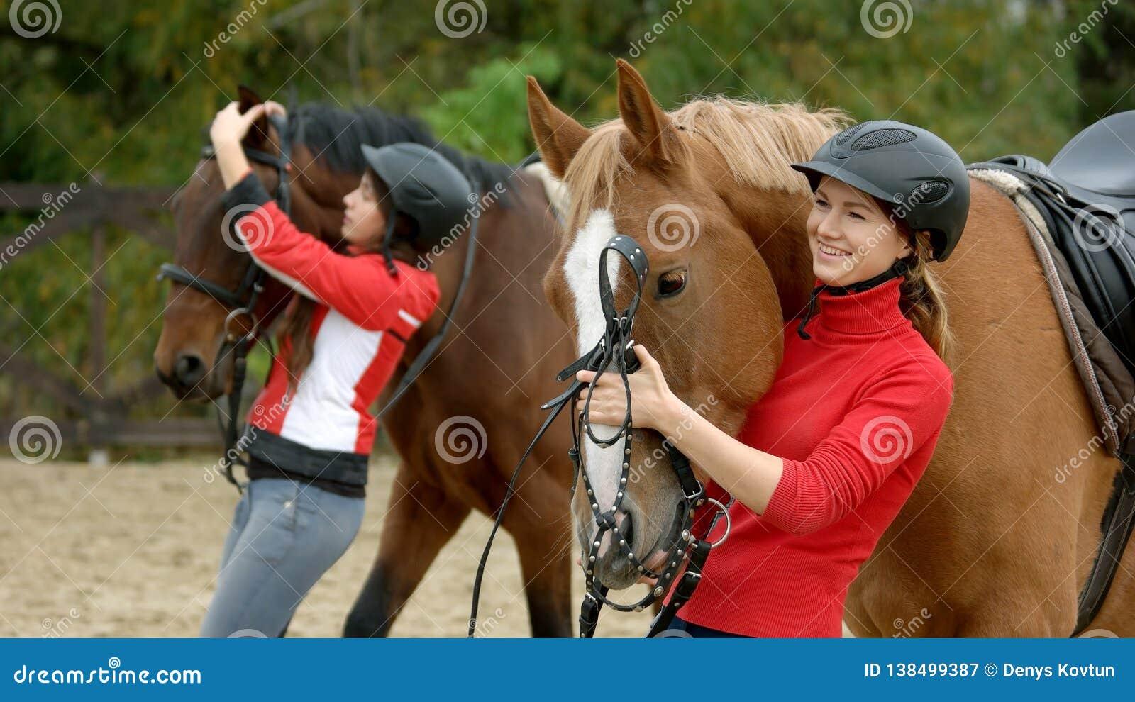 Милая усмехаясь девушка обнимая ее лошадь на ранчо