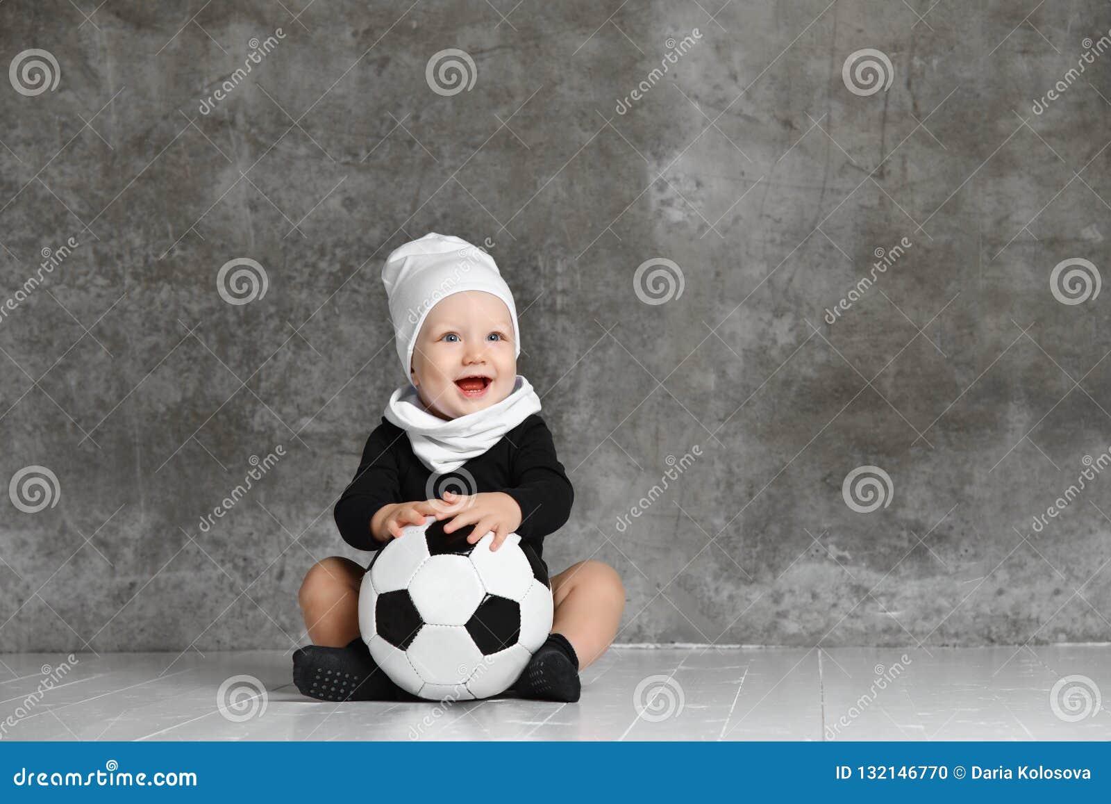 Милое изображение младенца держа футбольный мяч