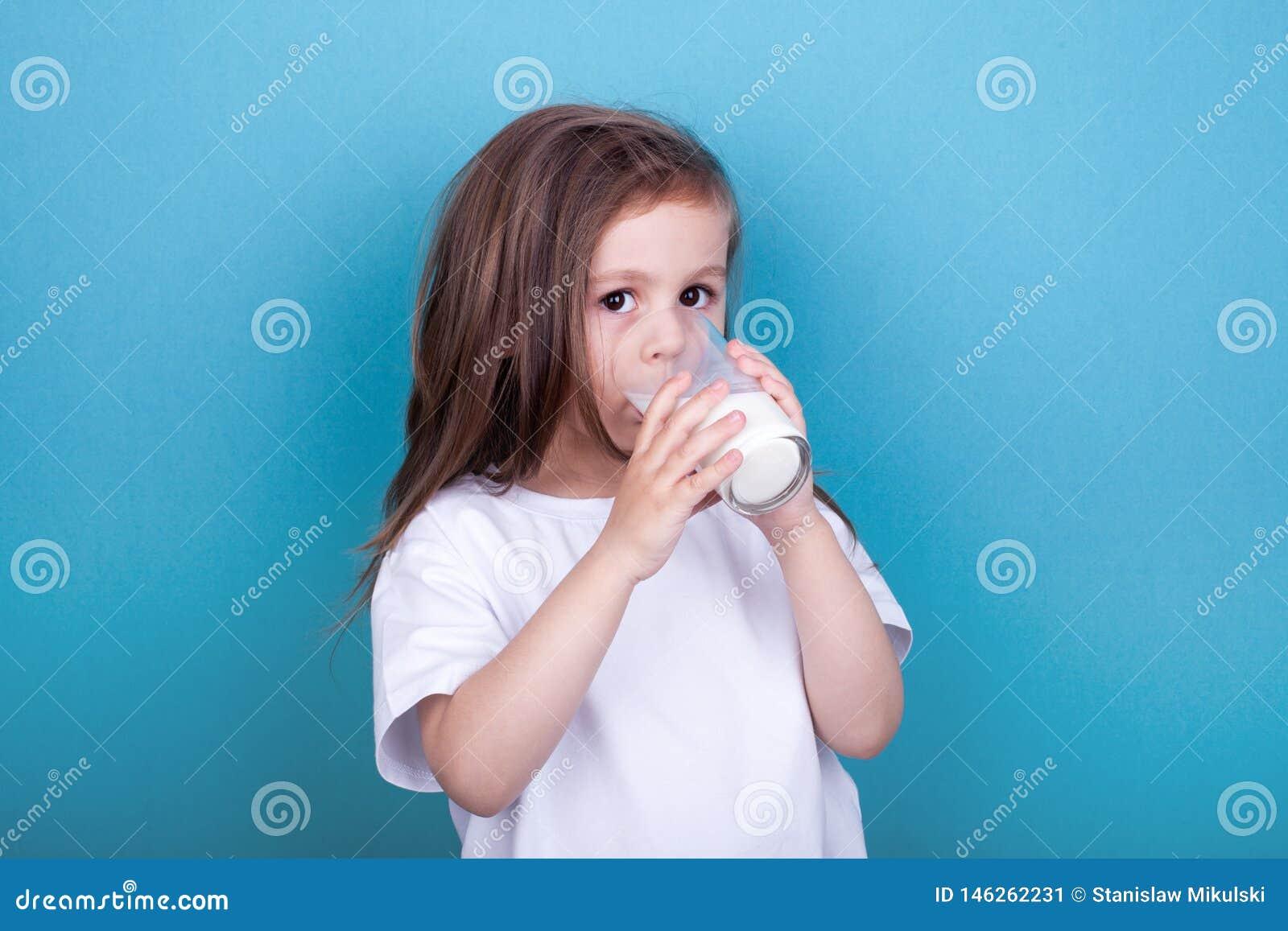 Милое питьевое молоко маленькой девочки от стекла