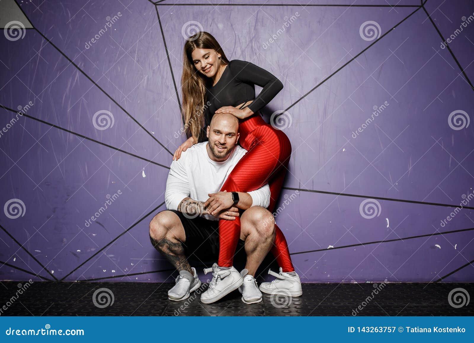 Милые атлетические пары Худенькая красивая девушка и сильный атлетический человек в одеждах спорт обнимают на предпосылке