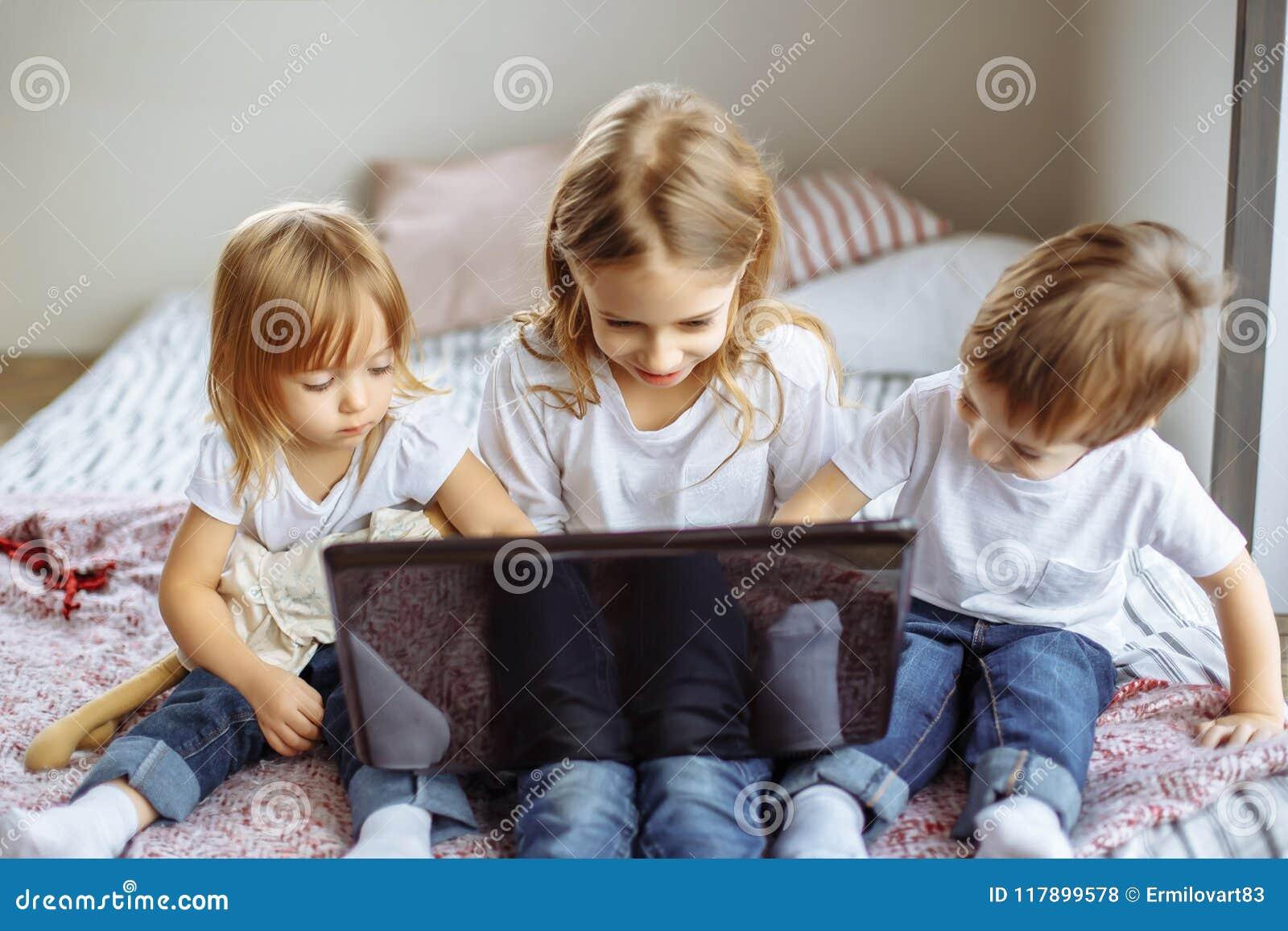 Милые дети используя компьтер-книжку