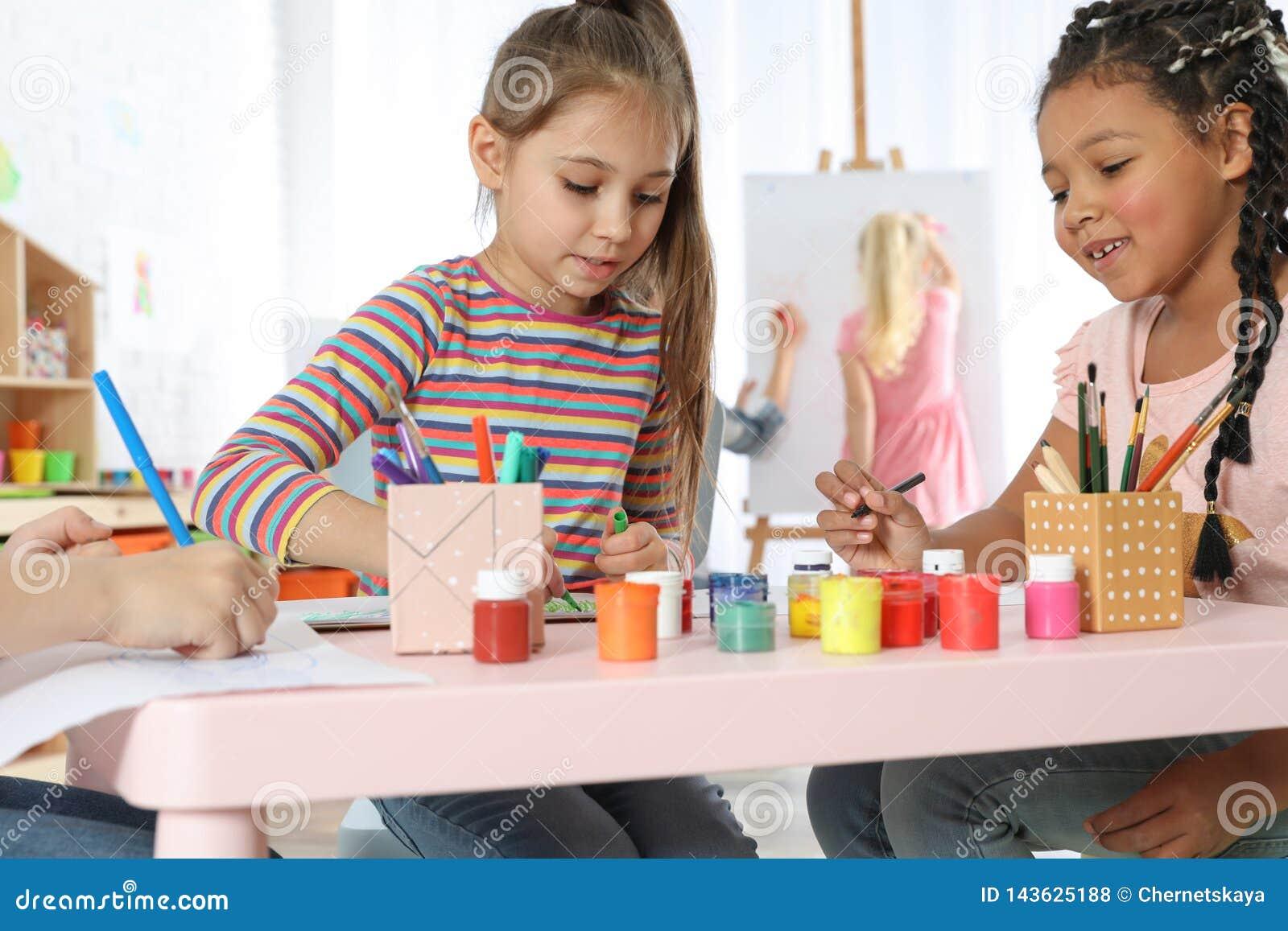 Милые маленькие дети рисуя на крася уроке