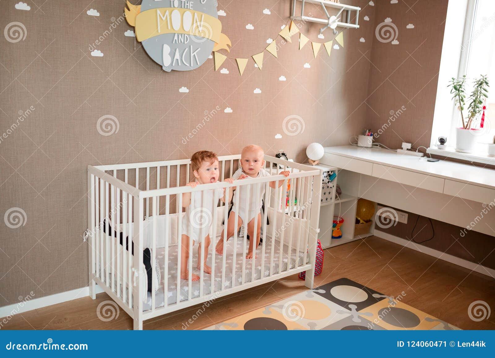 Милые маленькие младенцы смотря из кровати