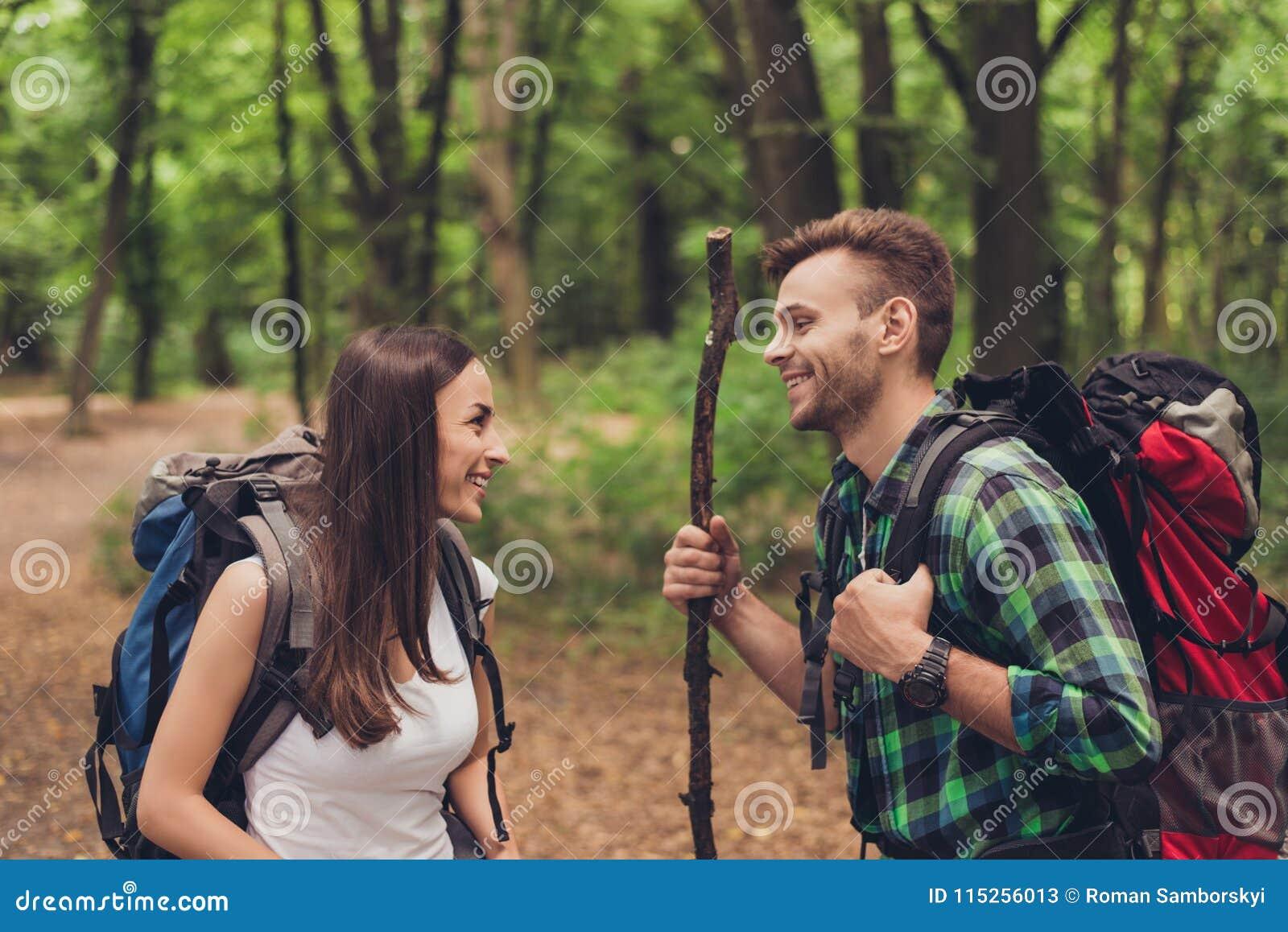Милые excited любовники пеший в лесе весны, говоря и наслаждаясь, нося удобные обмундирования для пешего туризма, с рюкзаками