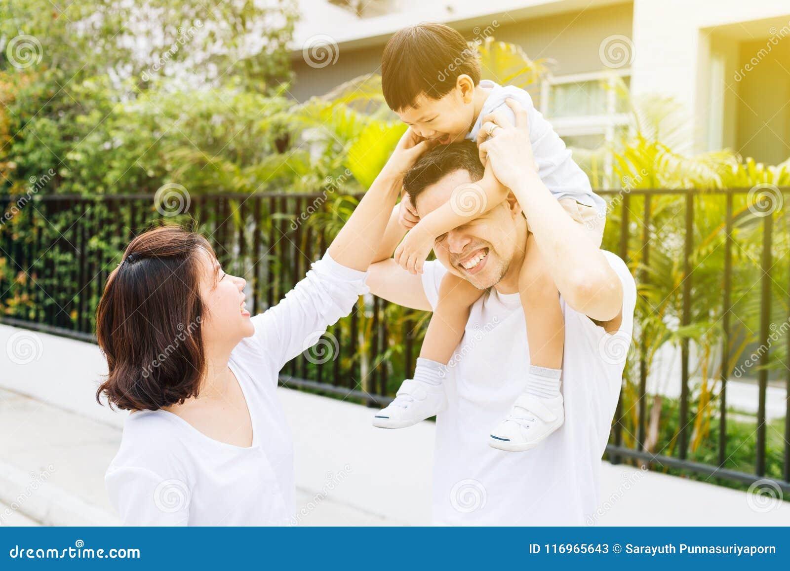 Милый азиатский отец piggbacking его сын вместе с его женой в парке Excited семья тратя время вместе с счастьем