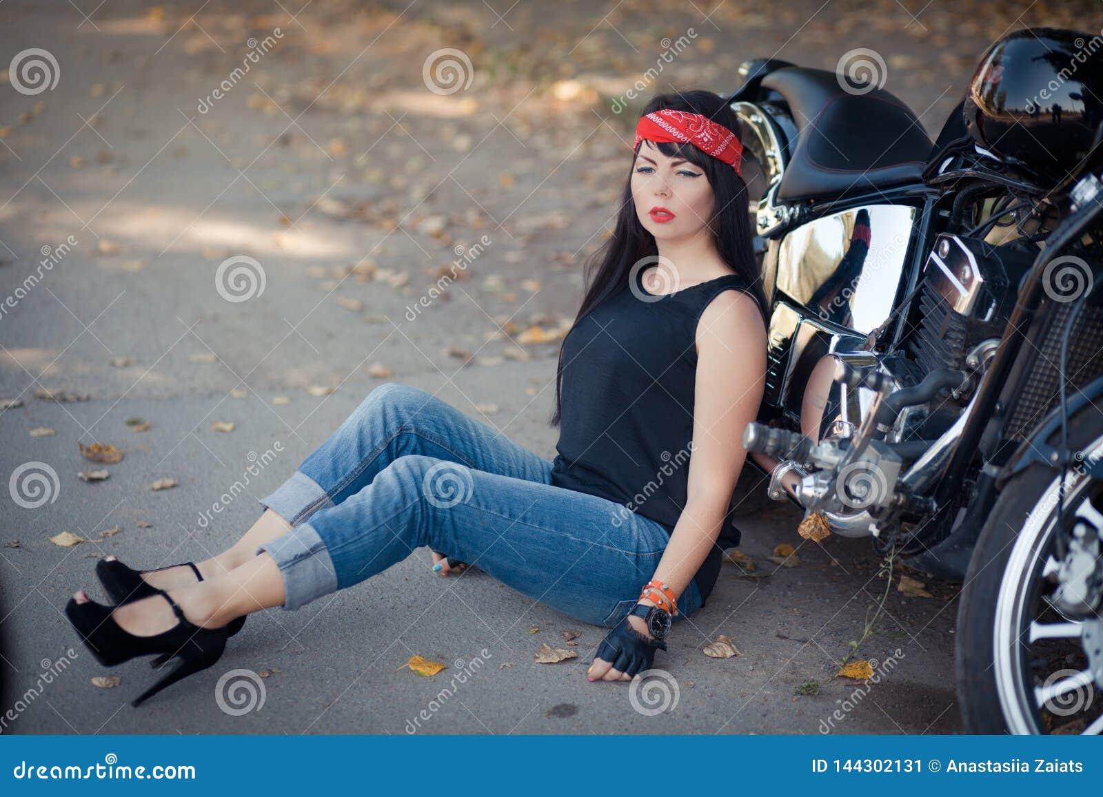 Милый велосипедист девушки или милая женщина с джинсами стильных, длинных волос нося сидя на поле на мотоцикле