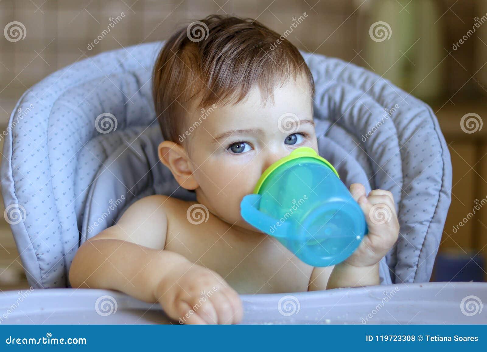 Милый голубоглазый ребёнок держа пластичную кружку в его руках и lookin питьевой воды самой на камере,
