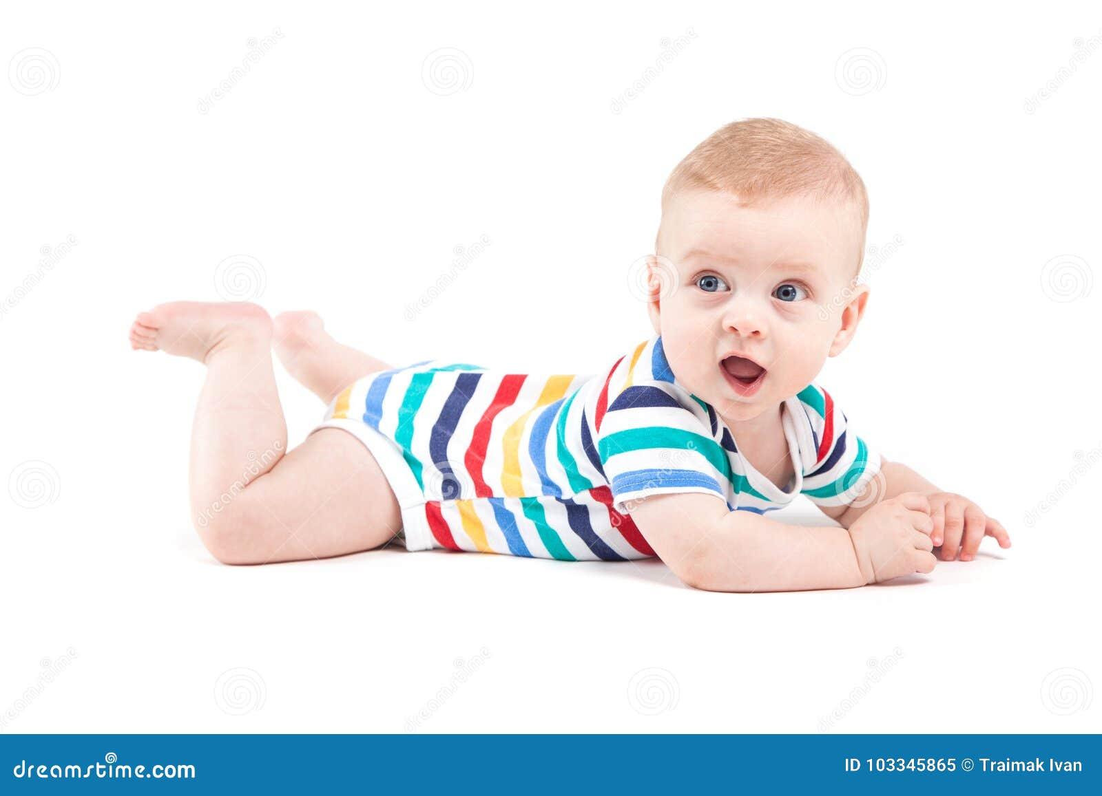 Милый изумленный мальчик в красочной рубашке лежит на животе