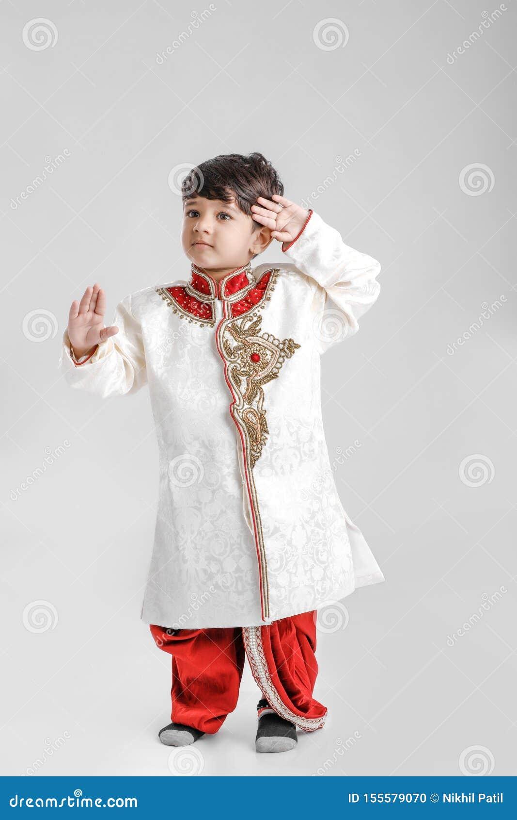 Милый индийский/азиатский мальчик в этнической носке и салютуя национальном флаге