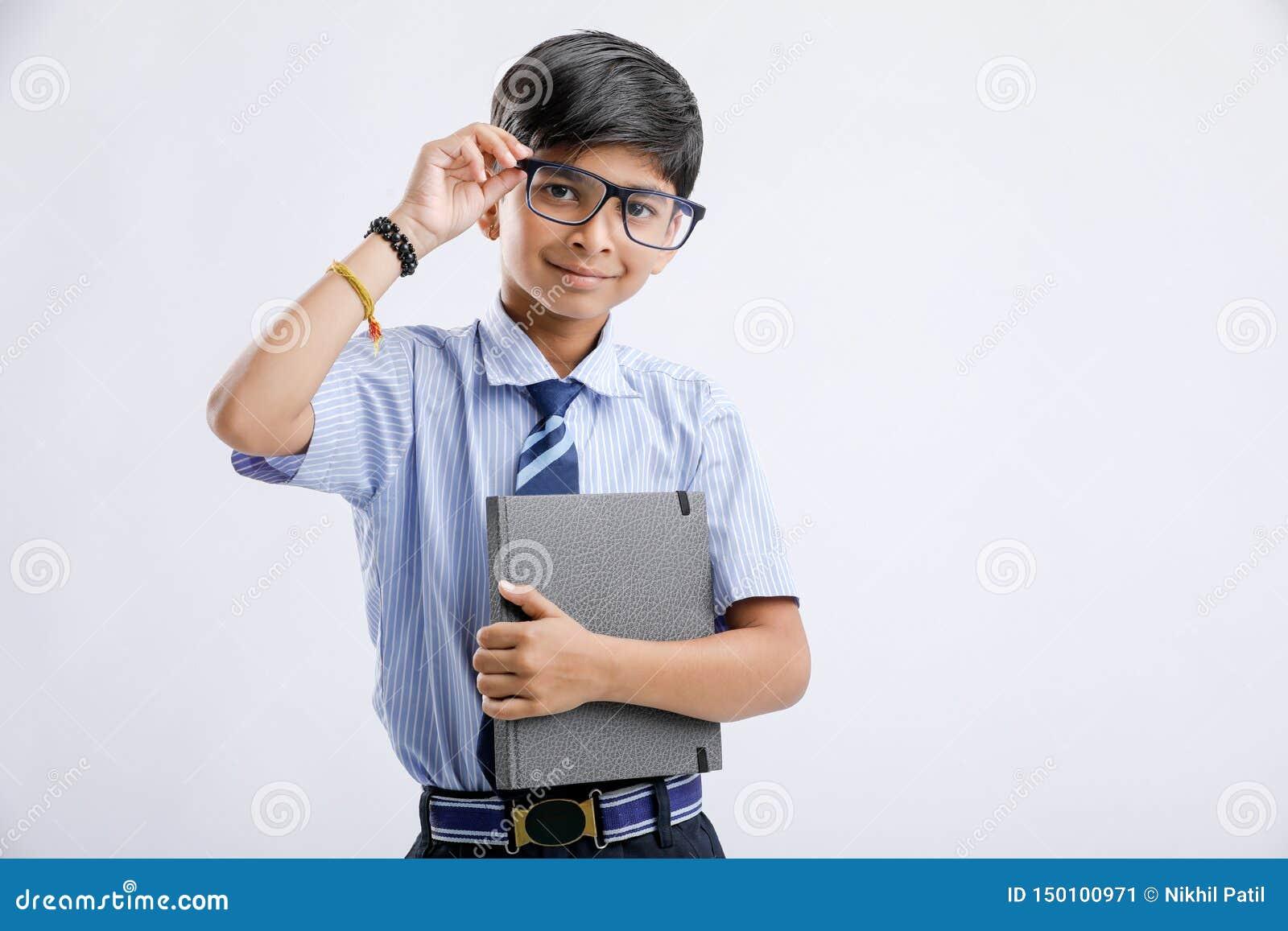 Милый маленький индийский/азиатский школьник с блокнотом изолированным над белой предпосылкой
