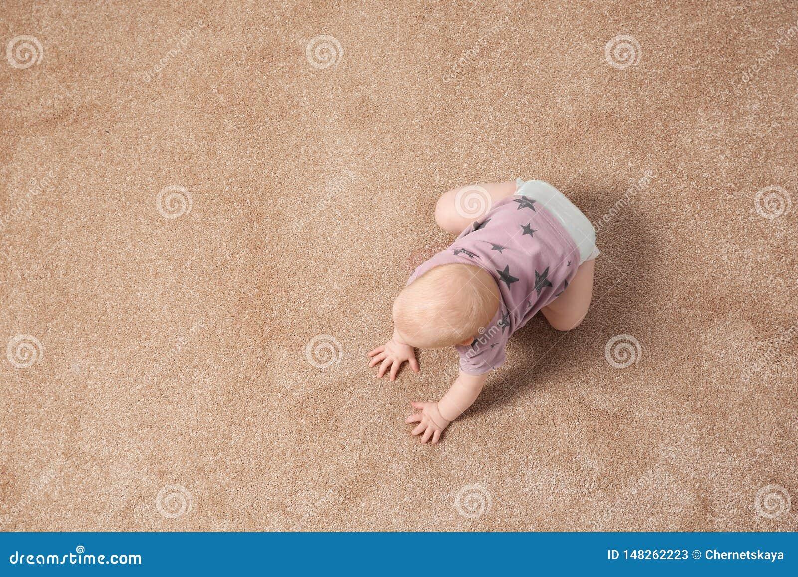 Милый маленький младенец вползая на ковре внутри помещения