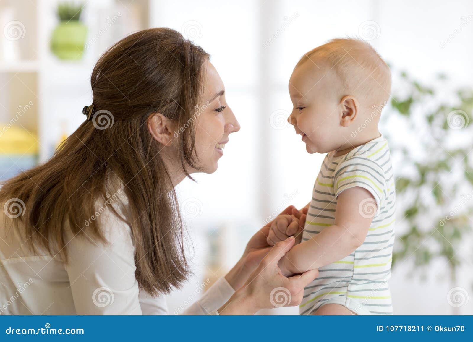 Милый маленький младенец играет с его молодой мамой