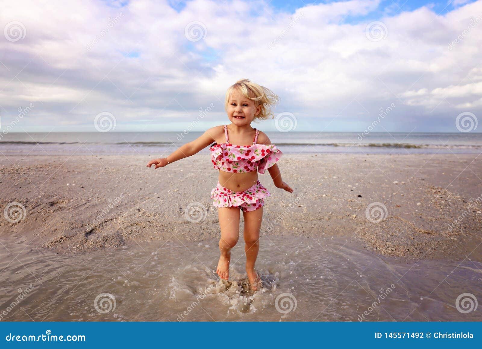 Милый маленький ребенок брызгая и играя в воде на пляже океаном