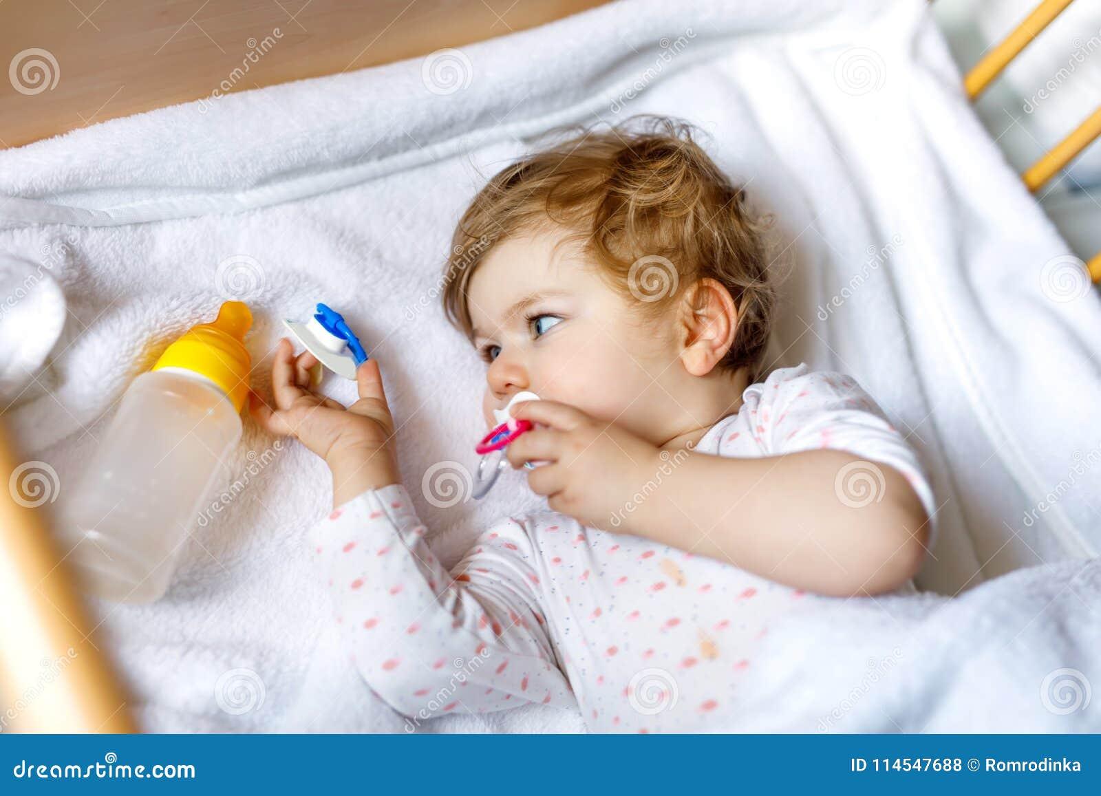 Милый маленький ребёнок держа бутылку с формулой слабый и выпивать Ребенок в кровати кроватки младенца перед спать