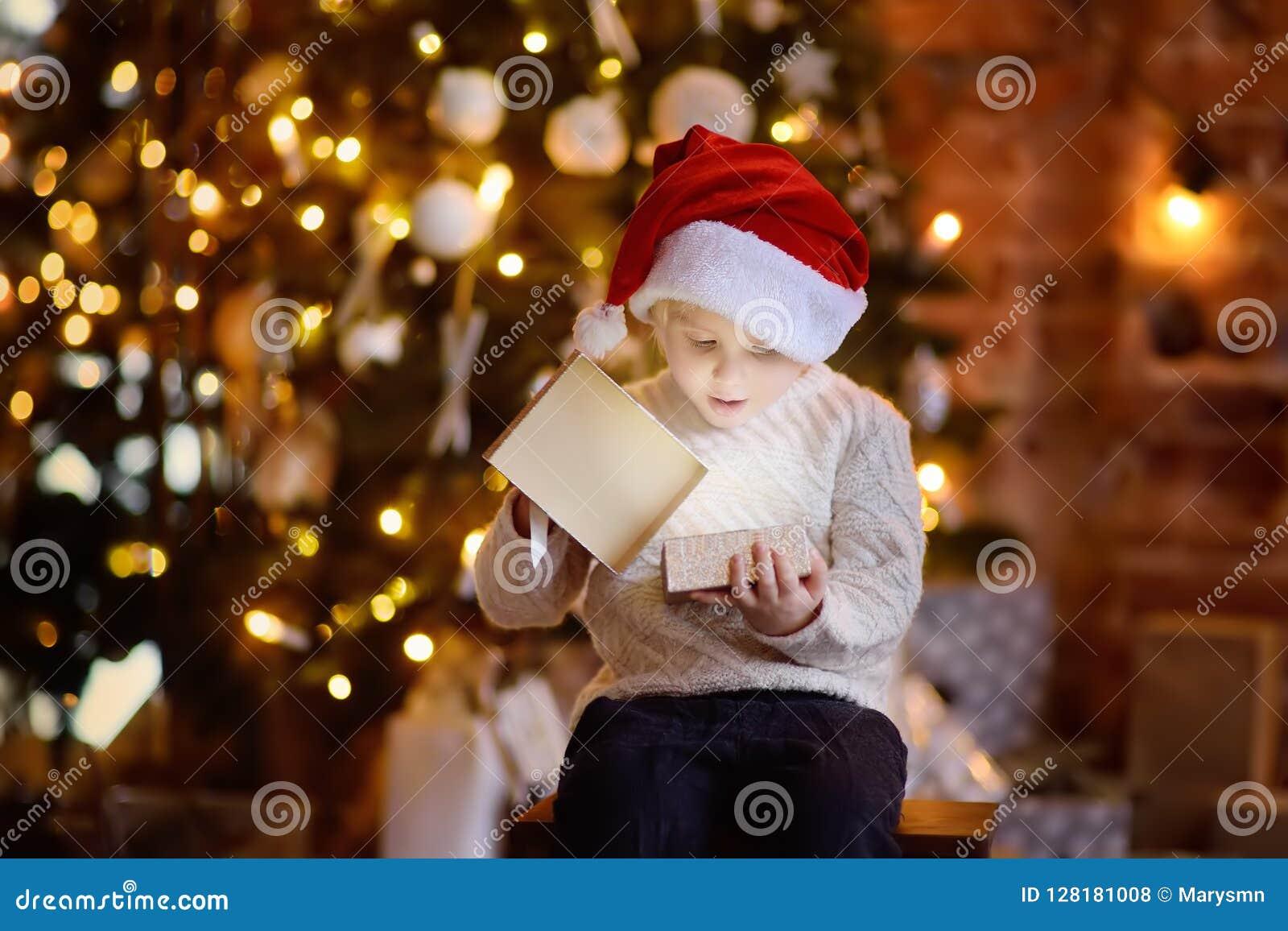 Милый мальчик нося шляпу Санты раскрывая подарок рождества