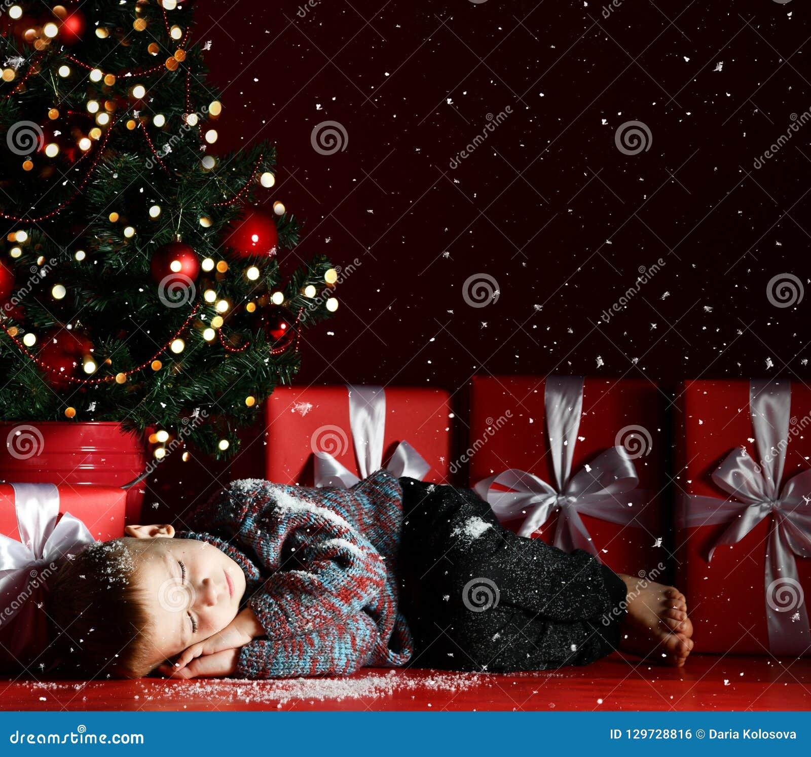 Милый мальчик упал уснувший под рождественской елкой ждать Санта Клаусом Время для чудес