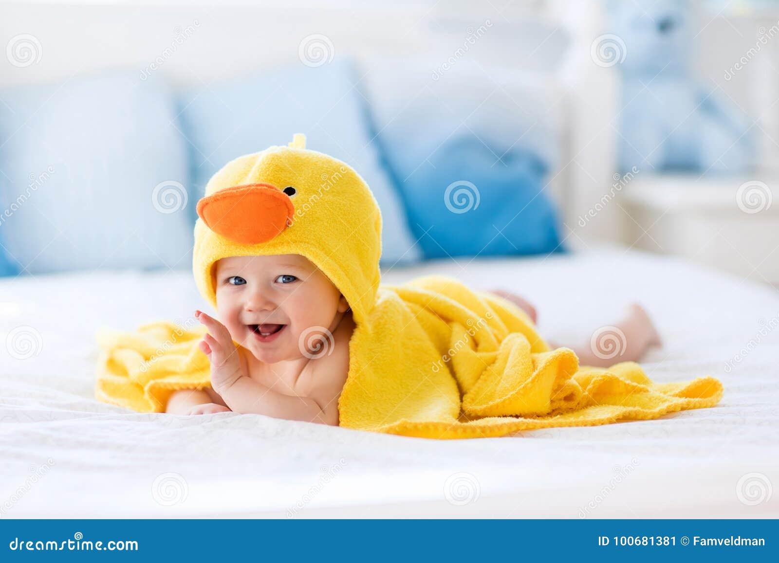 Милый младенец после ванны в желтом полотенце утки