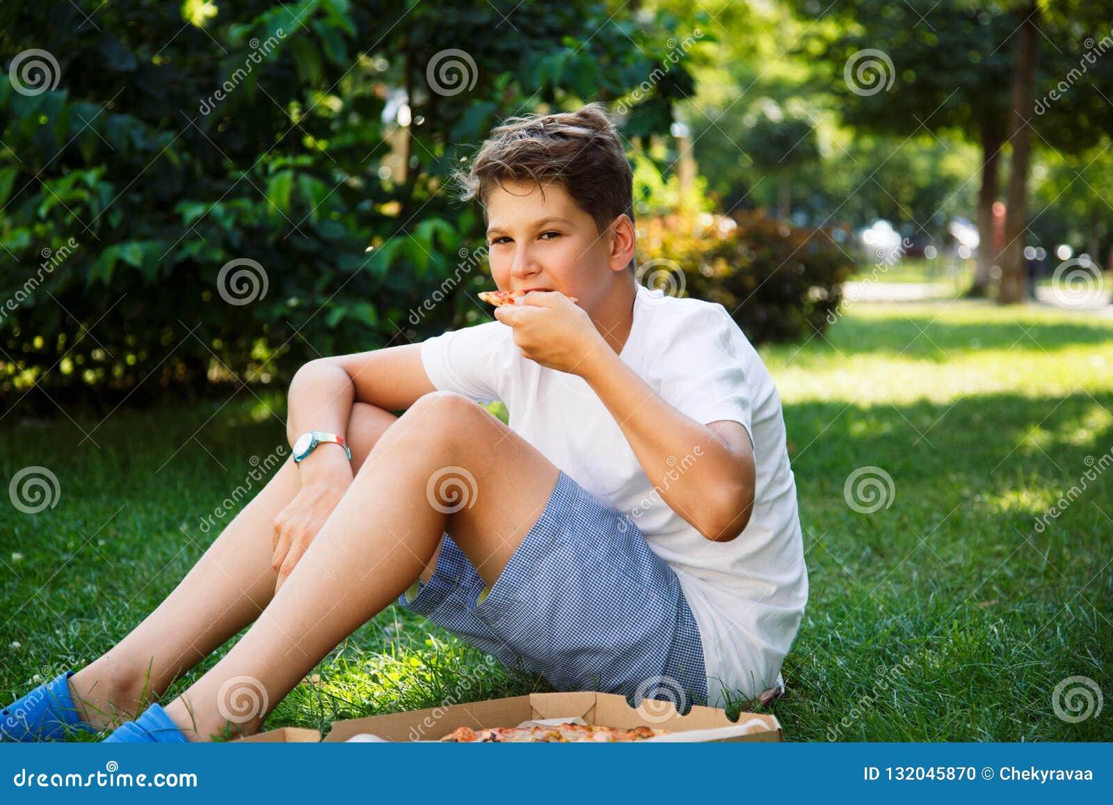 Милый, молодой мальчик в белой футболке сидит на траве и принимает кусок пиццы в парке