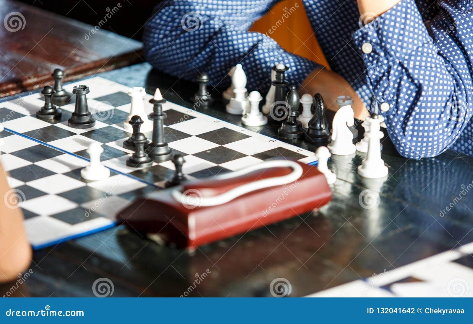Милый молодой умный мальчик в голубой рубашке играет шахматы на тренировке перед турниром летнего лагеря шахмат хобби