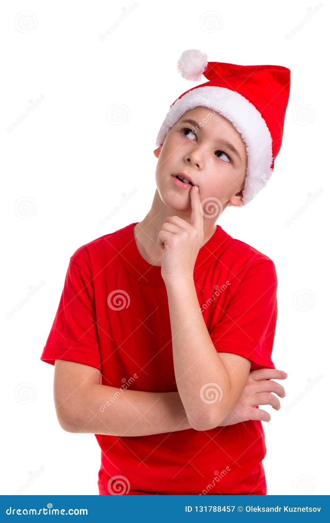 Милый озадаченный смотря мальчик, шляпа santa на его голове, с пальцем около губ Концепция: рождество или С Новым Годом!