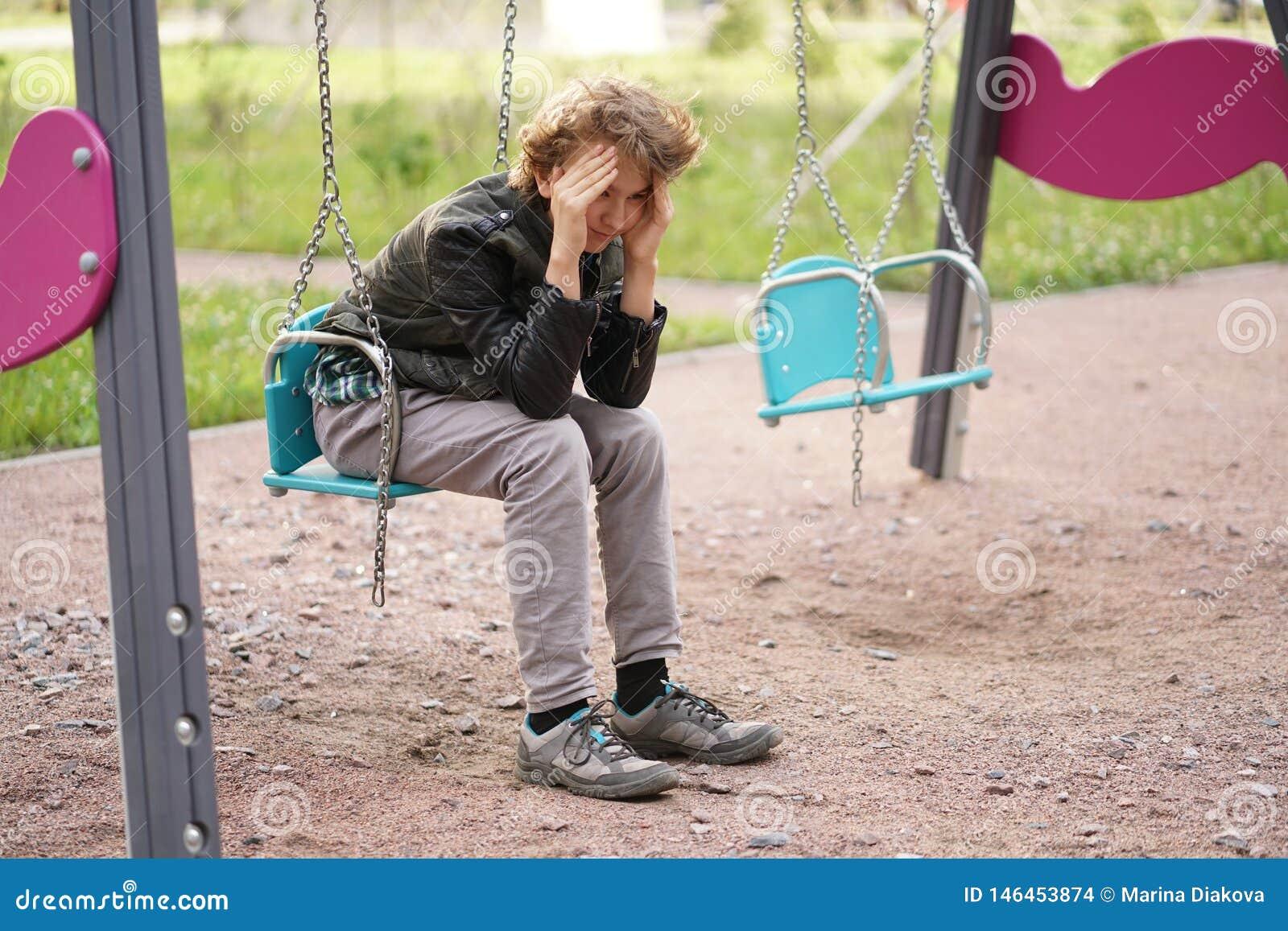 Милый положительный подросток мальчика на спортивной площадке в городе самостоятельно