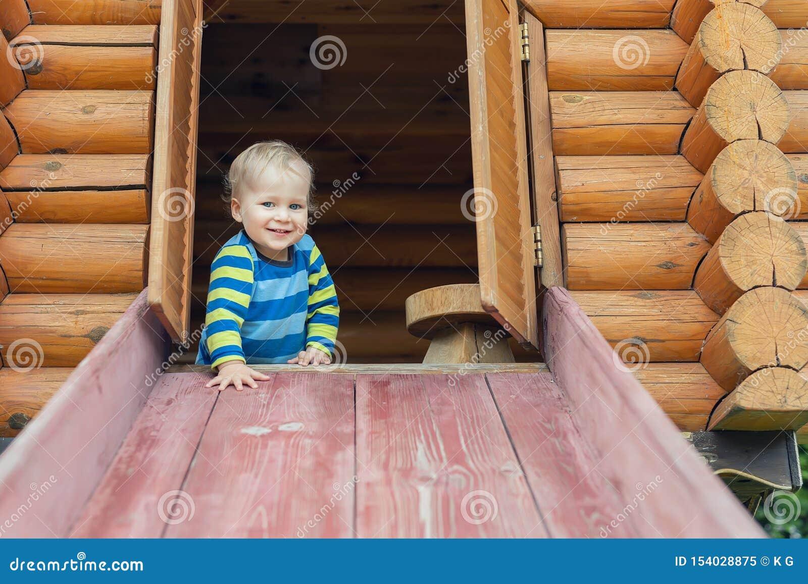 Милый прелестный кавказский мальчик малыша имея потеху сползая вниз деревянное скольжение на дружественную к эко естественную спо