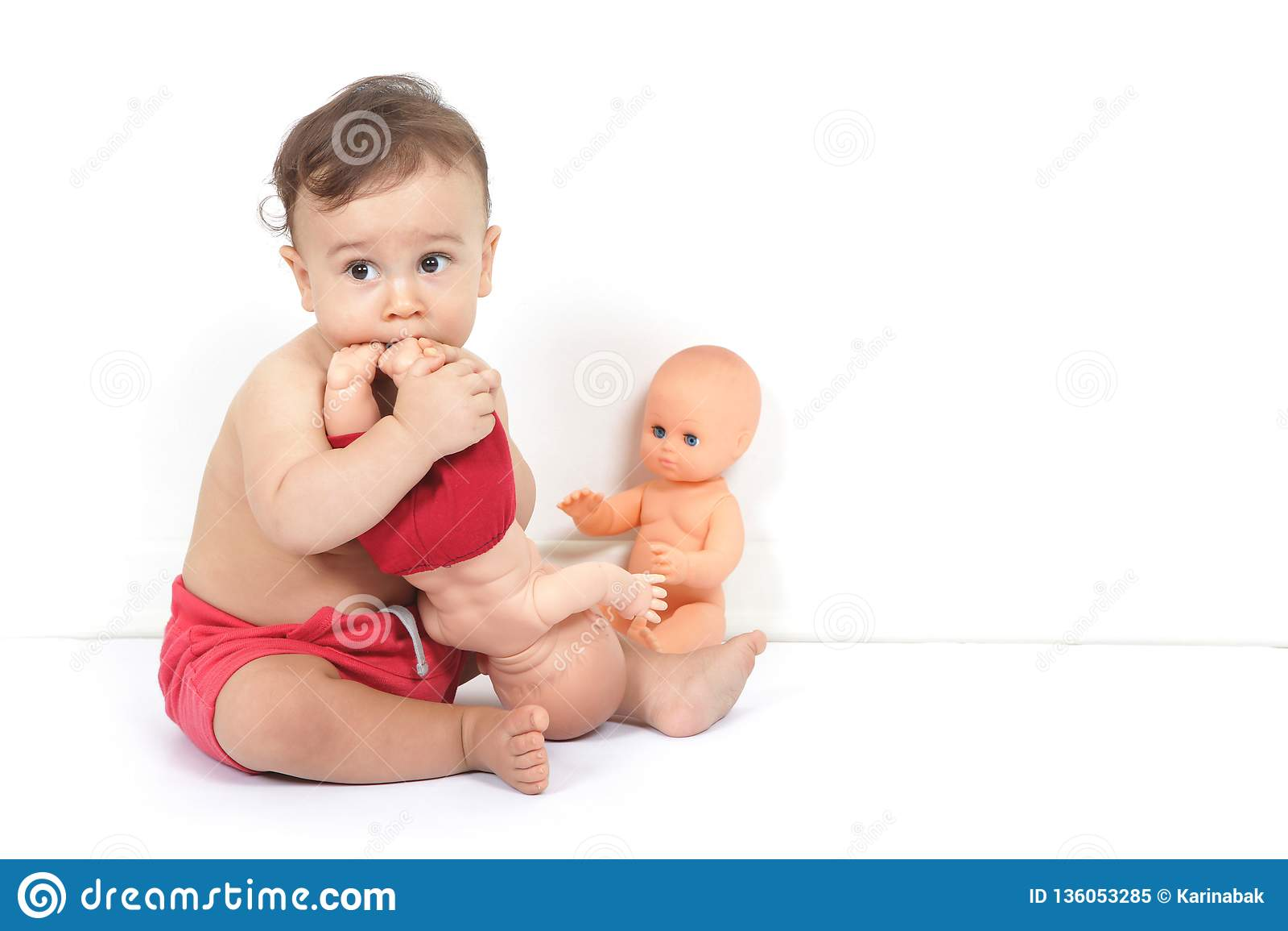 Милый ребенок играет с игрушками и пробует их