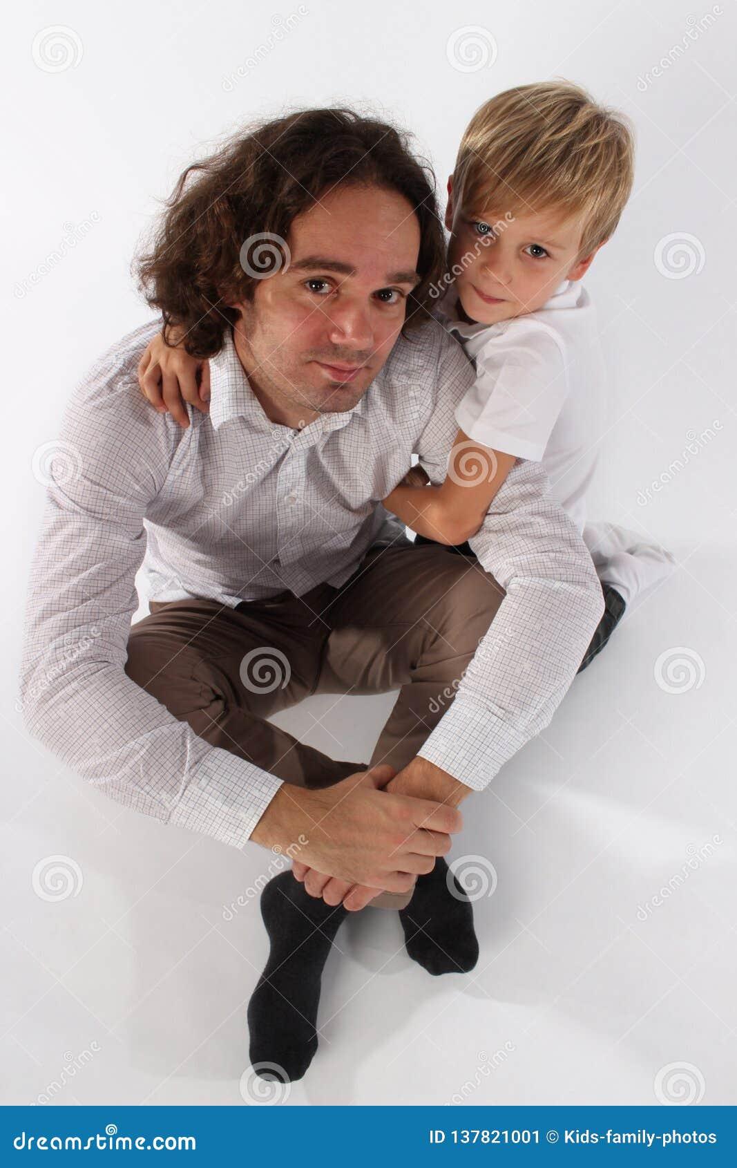 Милый справедливый мальчик ребенка волос обнимая его папы