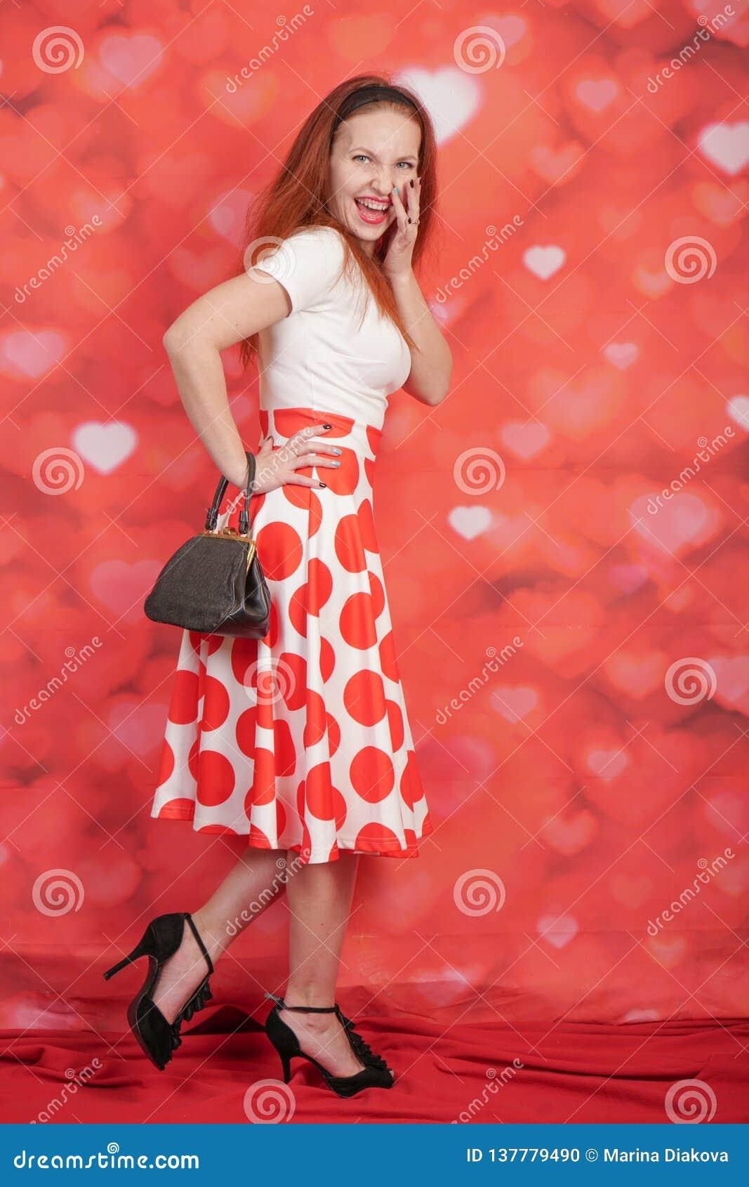 Милый стильный штырь вверх по девушке в белой рубашке и красное положение юбки точки польки винтажное на красной предпосылке серд