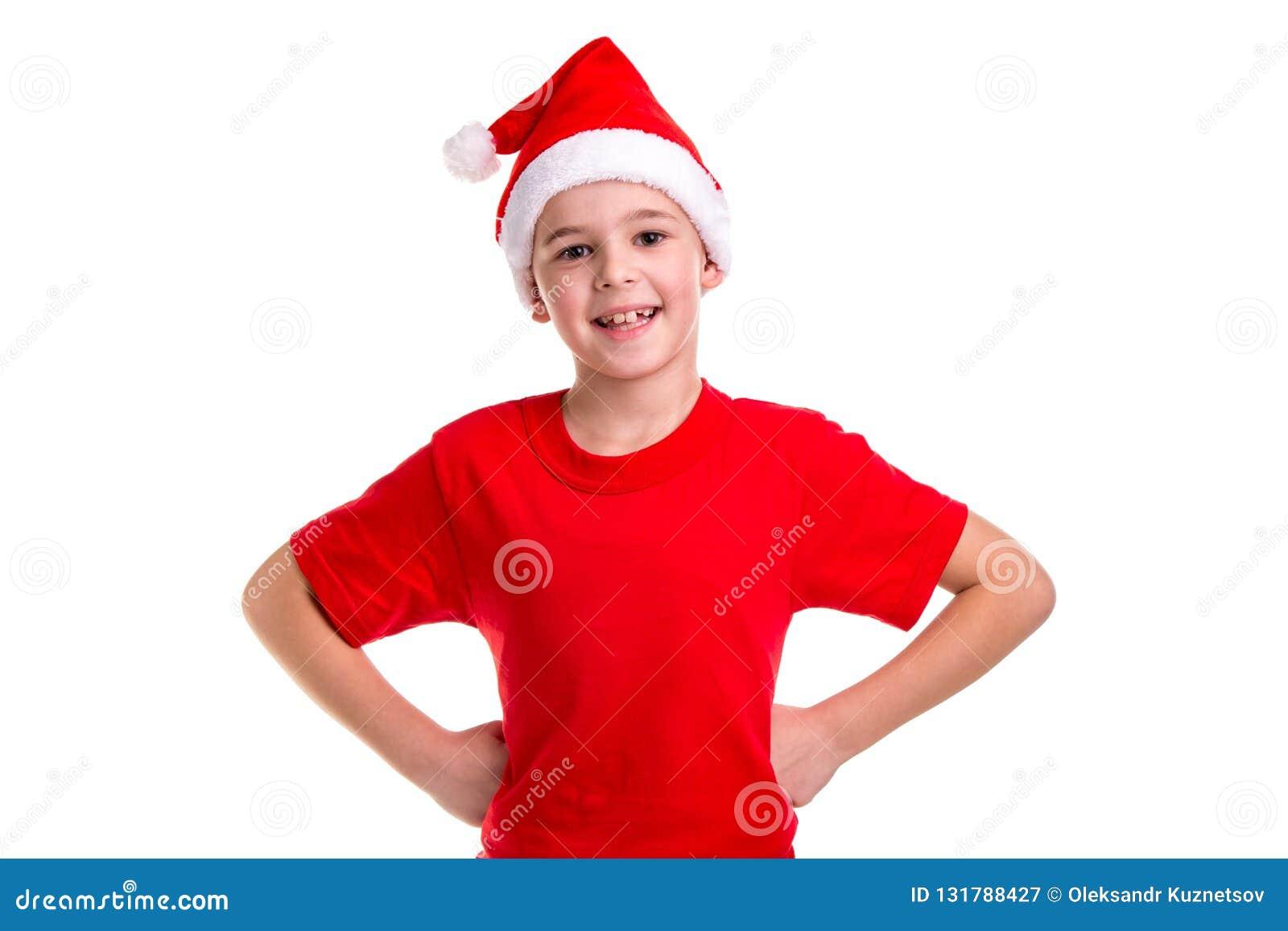 Милый усмехаясь мальчик, шляпа santa на его голове, с оружиями на концепции талии: рождество или С Новым Годом! праздник