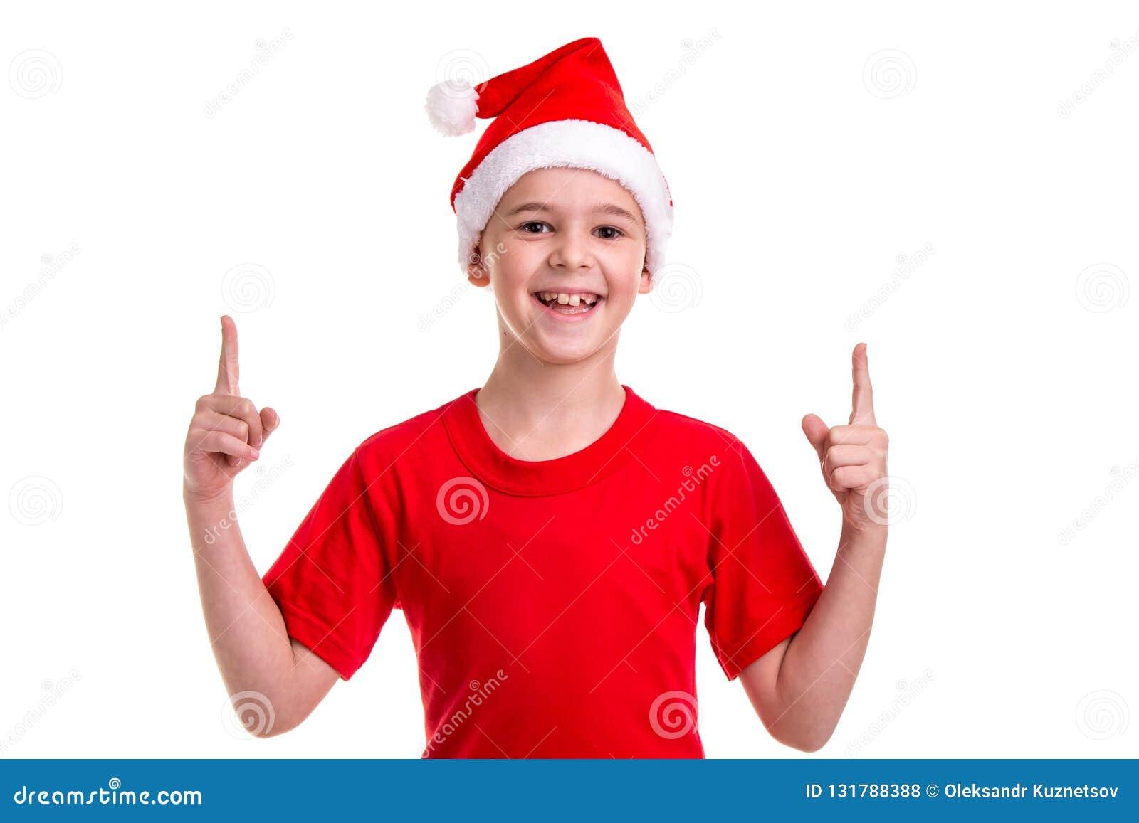 Милый усмехаясь мальчик, шляпа santa на его голове, с указывая пальцами вверх Концепция: рождество или С Новым Годом! праздник