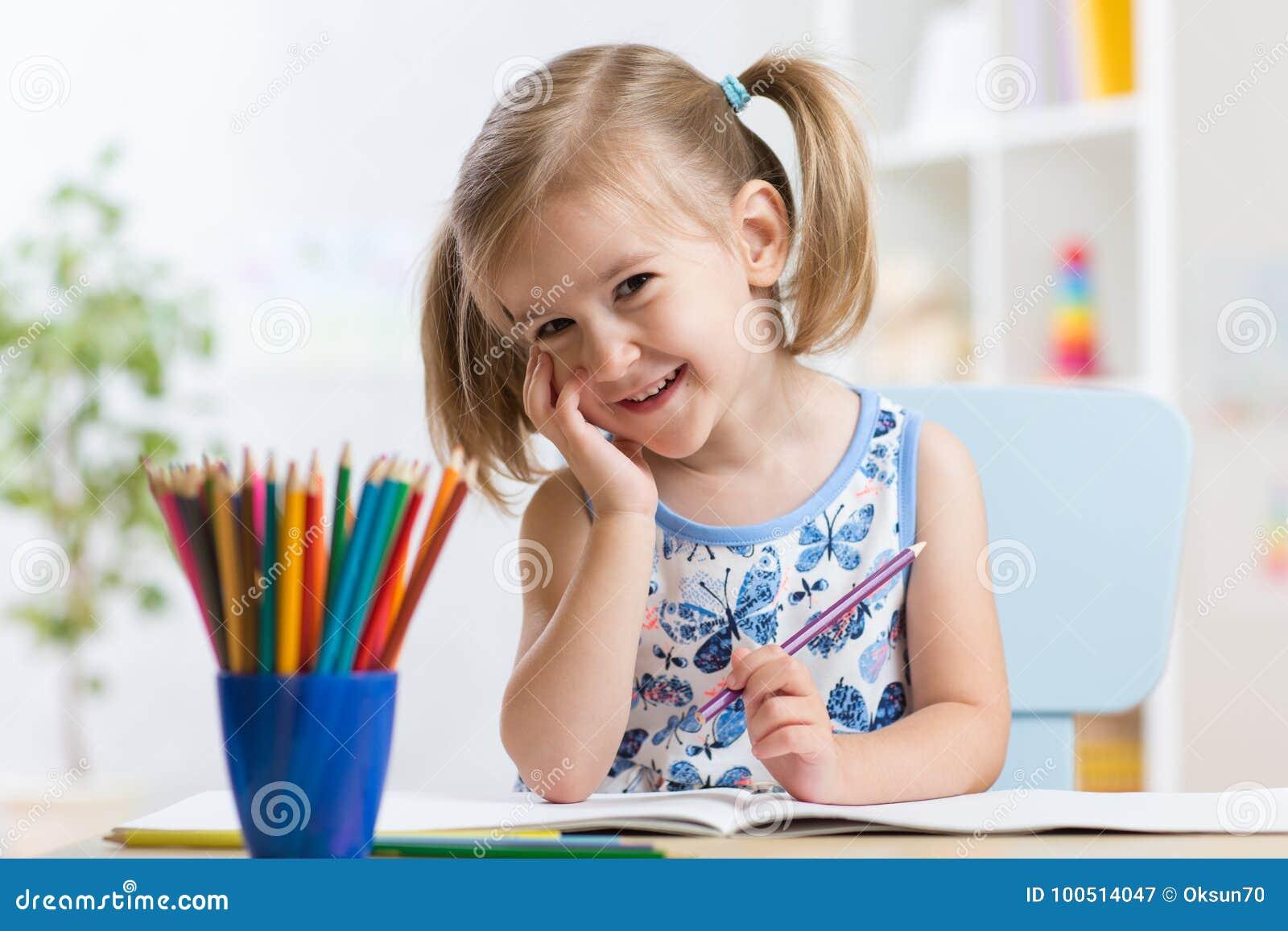 Милый чертеж маленькой девочки с красочными карандашами на бумаге Милый ребенок крася внутри помещения дома, daycare или детский