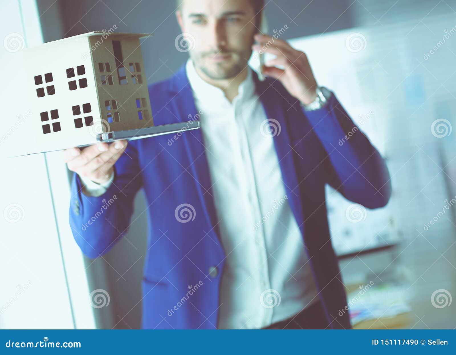 Миниатюра дома удерживания бизнесмена в наличии стоя в офисе