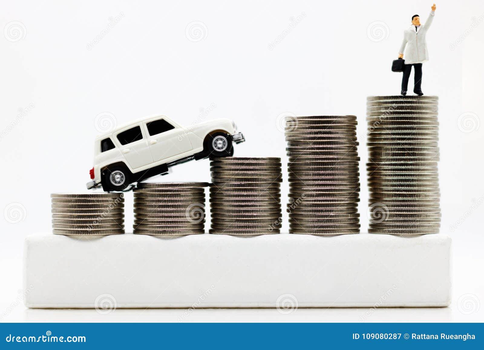 Миниатюрные люди: Бизнесмены na górze денег монетки с автомобилем