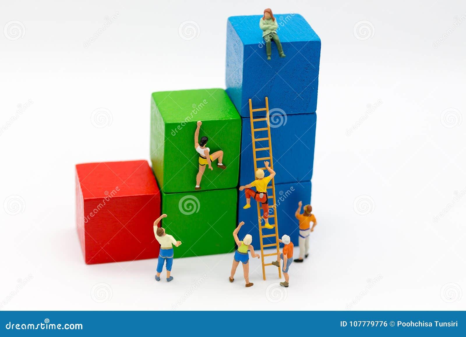 Миниатюрные люди: Спортсмены группы используют лестницы для того чтобы взобраться красочное деревянное здание Отображайте польза
