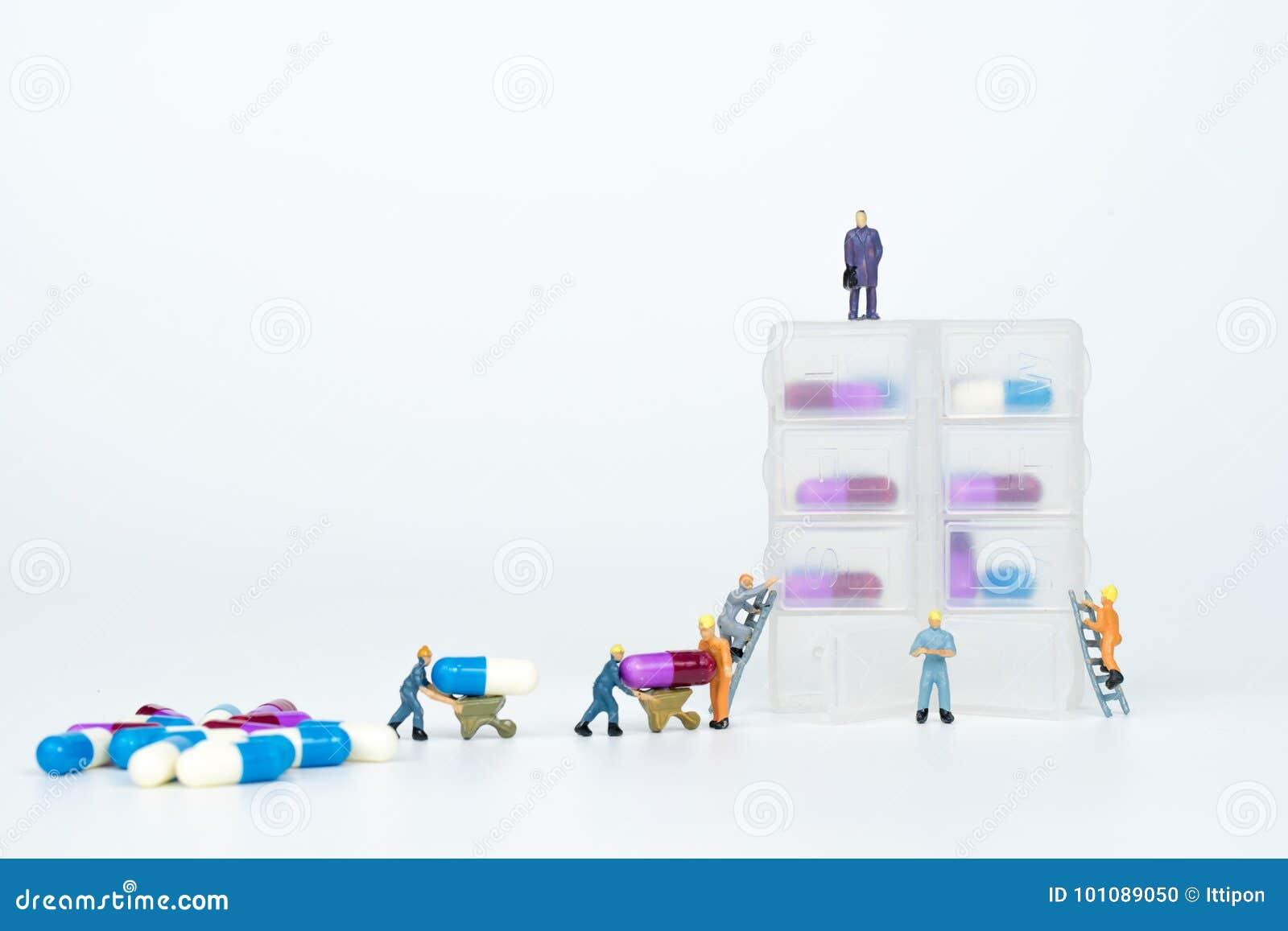 Миниатюрные люди с лекарства контейнером ежедневно