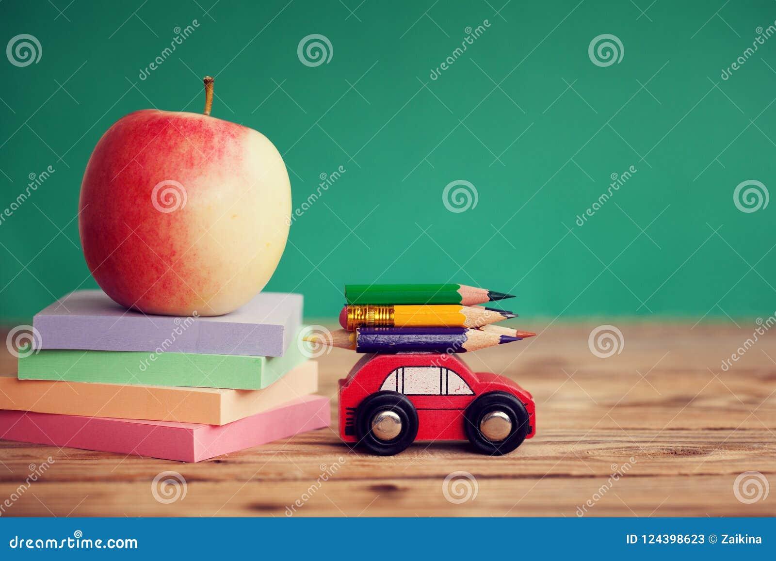 Миниатюрный красный носить автомобиля красочные карандаши и красные бумаги яблока и стога на деревянном столе задняя школа принци