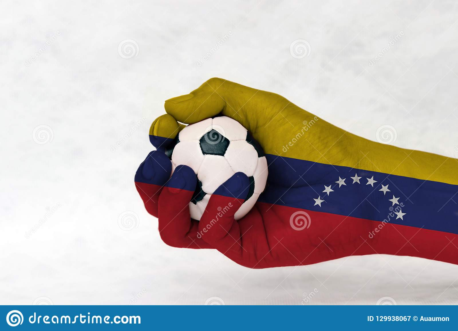 Мини шарик футбола во флаге Венесуэлы покрасил руку на белой предпосылке
