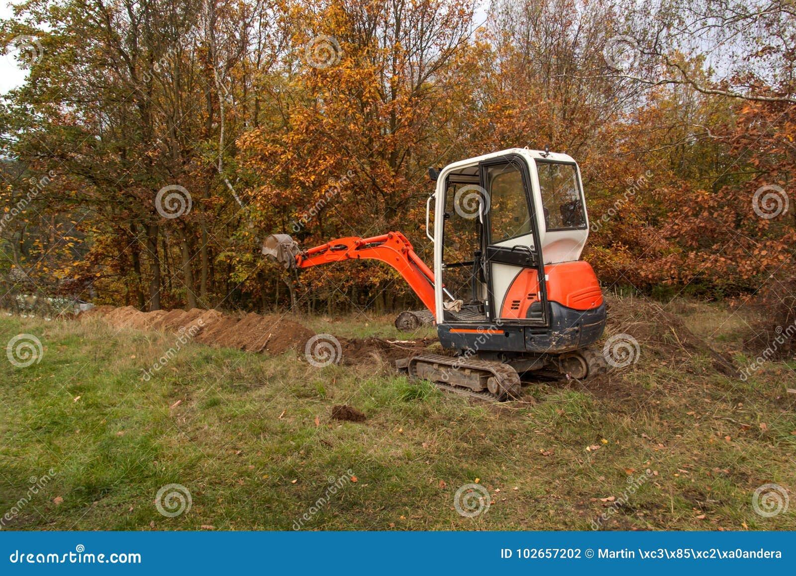 Мини экскаватор на строительной площадке Конструкция дома семьи около леса