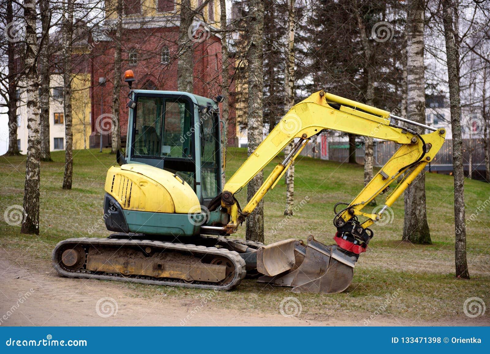 Мини экскаватор на строительной площадке Экскаватор стоит около выкопанного отверстия